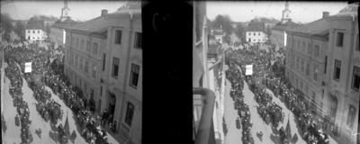 'Bildtext: ''Demonstrationer på 1 maj.'' :: Gatuvy med demonstrationståg med plakat med texten ''BRÖD''. Vy med folksamling och hus. Ev. kyrka. ::  :: Ingår i serie med fotonr. 5261:1-14. Se även hela serien med fotonr. 5237-5267.'