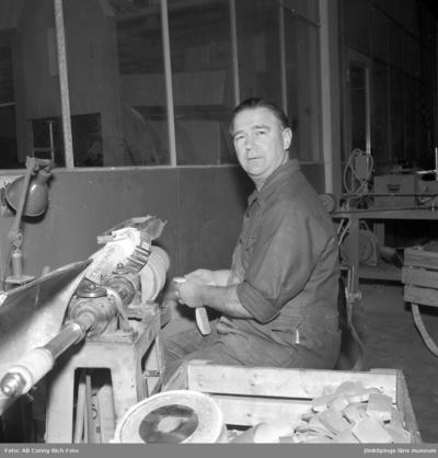 En man sitter vid en maskin och arbetar på Huskvarna Borstfabrik.