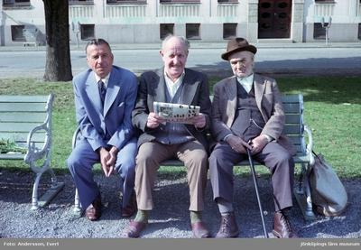 Olle Blom, i mitten, sitter på en parkbänk på Esplanaden i Huskvarna och läser i tidningen Expressen om en kupp av TV2.