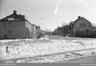 En vinterbild med bostadshus utmed en gata i Huskvarna. Höga snövallar är upplogade utmed gatan.