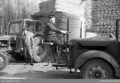 En man lastar virke med en egen lösning på lyftkran och Nils Daag står framför en traktor med med lastat släp.