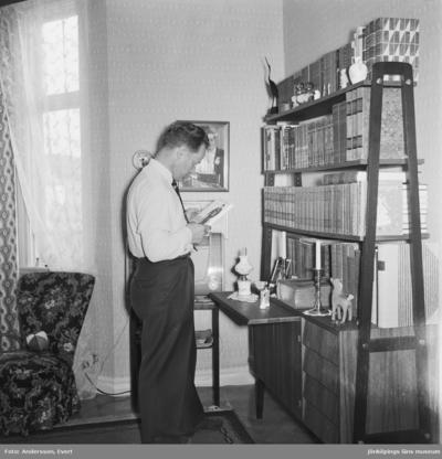 Interiör från fotograf Evert Anderssons hem på Odengatan 22 i Huskvarna. Evert står vid bokhyllan och har plockat fram en bok.