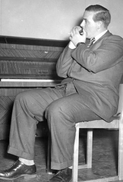 Man vid pianot spelande på sitt munspel. Bilden ingår i ett fotoalbum.