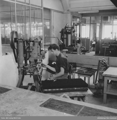 Folke Berg sitter vid maskinen och arbetar, på Huskvarna Borstfabrik.