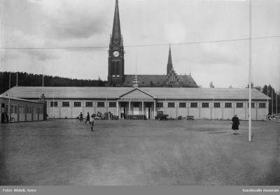 En svit bilder som visar mässområdet för Sundsvallsutställningen 1928. Bild 1. Maskinhallen på Läroverksplanen. Bild 2. Automobilutställningshallen (i vinkel mot maskinhallen). Bild 3. Interiör av maskinhallen. Bild 4. Restaurangen i skolparken (Handelsskolan till vänster). Bild 5. Restaurangen (se föregående bild). Bild 6. G A-skolans gymnastikhus (användes som mässhall). Bild 7. Nöjesfältet med utsiktstorn och ruschkanor. Bild 8. Viadukten över järnvägen mellan skolorna Läroverket och G A-skolan.