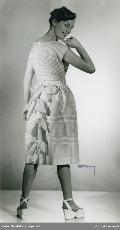 e2261d5dc0a5 Modell i randig klänning med rosetter i ryggen och platåskor.