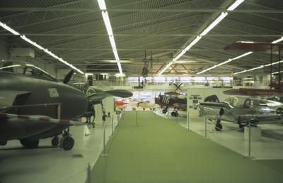 Interiör av Flygvapenmuseum, våren 1988. Mittgång och utställda flygplan längs sidorna.