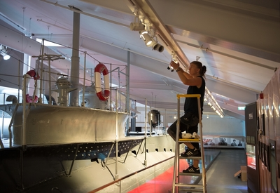 Pernilla Johansson sätter upp spotlights i ubåtshallen Marinmseum, Karlskrona