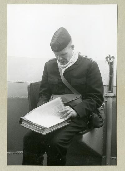 Bilden föreställer en uniformsklädd besättningsman som sitter med en pärm med papper i knät ombord på minfartyget Älvsnabben under långresan 1966-1967.