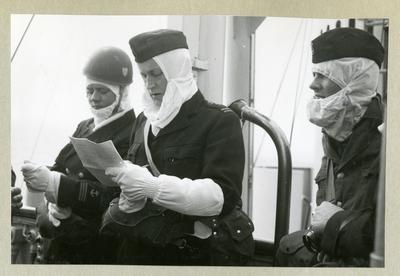 Bilden föreställer tre uniformsklädda besättningsmedlemmar med vita huvor och handskar ombord på minfartyget Älvsnabben under långresan 1966-1967.