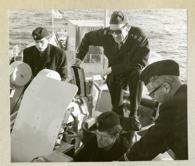 Bilden föreställer fyra uniformsklädda besättningmän vid en artilleripjäs ombord på minfartyget Älvsnabben under långresan 1966-1967.