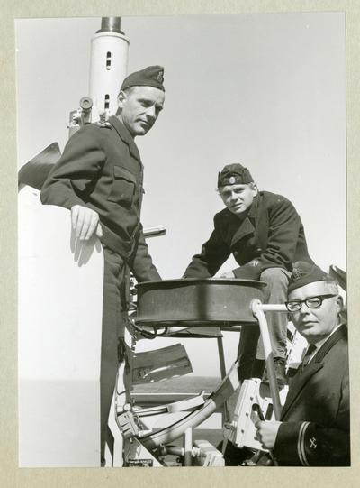 Bilden föreställer tre uniformsklädda besättningsmedlemmar vid en artilleripjäs ombord på minfartyget Älvsnabben under långresan 1966-1967.