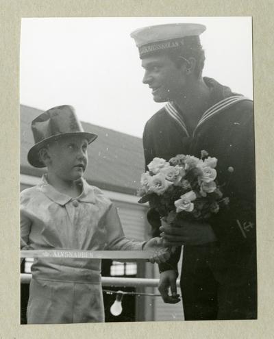 Bilden föreställer en liten pojke i hatt och Carl XVI Gustaf, klädd i uniform. I ena handen håller Carl XVI Gustaf en blombukett. Bilden är tagen under minfartyget Älvsnabbens långresa 1966-1967.