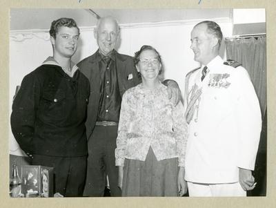 Bilden föreställer Carl XVI Gustaf, två män och en kvinna som poserar inför ett gruppfoto. Bilden är tagen under minfartyget Älvsnabbens långresa 1966-1967.