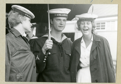 Bilden föreställer två kvinnor som står på varsin sida om Carl XVI Gustaf, som är klädd i uniform och håller i ett paraply. Bilen är tagen under minfartyget Älvsnabbens långresa 1966-1967.