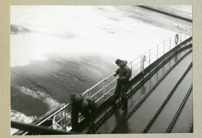 Bilden föreställer två ordentligt påklädda besättningmän ombord på minfartyget Älvsnabbens däck under långresan 1966-1967. På bilden befinner sig fartget på stormigt vatten till följd av orkanen Diana.