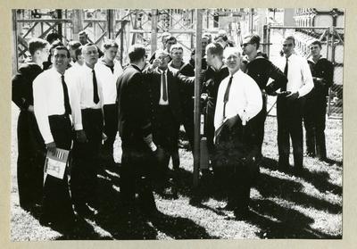 Bilden föreställer en grupp män som står samlade kring en man med rest hand. En del av männen är klädda i skjorta och slips medan de andra är klädda i uniform. Bilden är tagen under minfartyget Älvsnabbens långresa 1966-1967.