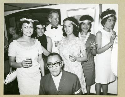 Bilden föreställer en grupp finklädda människor, bestående av två män och fem kvinnor. Om håret bär kvinnorna band med texten ÄLVSNABBEN. Bilden är tagen under minfartyget Älvsnabbens långresa 1966-1967.