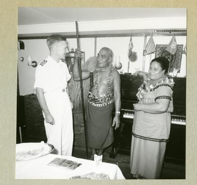 Bilden föreställer en besättningsman i vit uniform tillsammans med en man och kvinna i lokala kläder. Bilden är tagen i Pago-Pago i samband med minfartyget Älvsnabbens långresa 1966-1967.