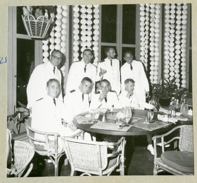 Bilden föreställer besättningsmän i vita uniformer som poserar för en gruppbild i samband med en middag. Bilden är tagen under minfartyget Älvsnabbens långresa 1966-1967.