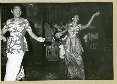 Bilden föreställer två kvinnor som framför en dans. I bakgrunden syns uniformsklädda män som åskådare. Bilden är tagen i Samoa i samband med minfartyget Älvsnabbens långresa 1966-1967.