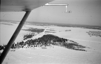 Flygfotografi av skogsparti och Veitsiluoto samhälle (i högerkant). Bild från F 19, Svenska frivilligkåren i Finland. Med flygplansvinge i förgrunden.