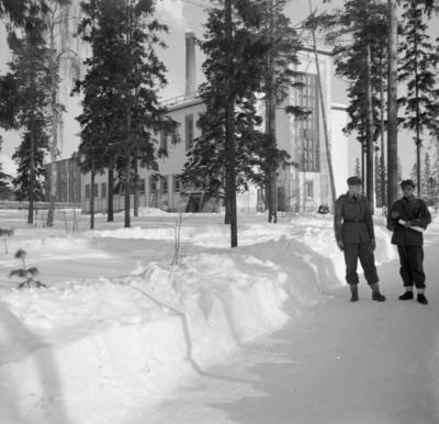 Två militärer vid F 19, Svenska frivilligkåren i Finland står utanför en väg utanför en byggnad.