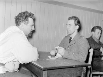 Två militärer ur F 19, Svenska frivilligkåren i Finland samtalar vid ett fikabord.