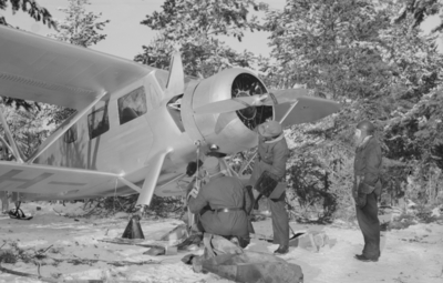 Klargöring av flygplan Waco ZQC-6 vid F 19, Svenska frivilligkåren i Finland. Flygmekaniker i arbete. En flygare i flygdräkt står vid sidan om.