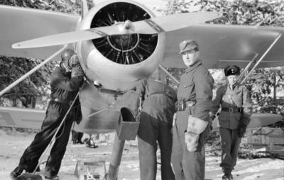 Mekanikerarbete med flygplan Waco ZQC-6 vid F 19, Svenska frivilligkåren i Finland. Fyra militärer vid flygplanet.