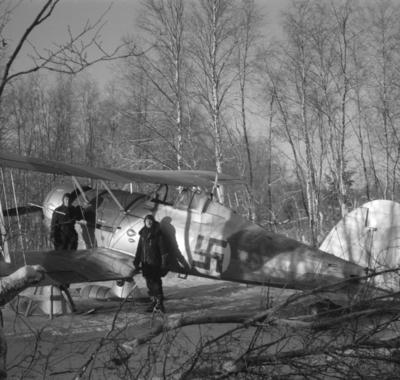 Flygplan Gloster Gladiator märkt K vid F 19, Svenska frivilligkåren i Finland. Oidentifierad militör samt flygförare Arne Frykholm vid flygplanet. Vy snett bakifrån.