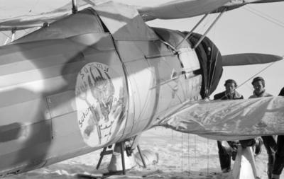 Flygplan Gloster Gladiator gul A, tillhörande F 19, Svenska frivilligkåren i Finland, märkt med 'Sammy Satana Perkele'. Vy av sidan, snett bakifrån. Två män står vid flygplansvingen.
