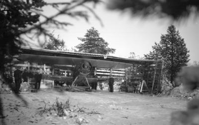 Flygplan Hawker Hart blå R i värn vid F 19, Svenska frivilligkåren i Finland. Flygplanet har påhängda bomber och varmkörs inför start. Fyra militärer i arbete vid flygplanet. I flygplanet sitter Åke Mörne och Hugo Beckhammar.