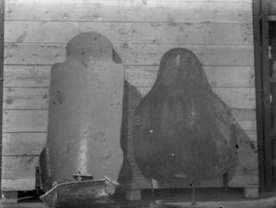Ryggpansar och pansarplåt från flygplan står uppställda vid en vägg inomhus, under finska vinterkriget, 1940. Bild från Svenska frivilligkåren i Finland.