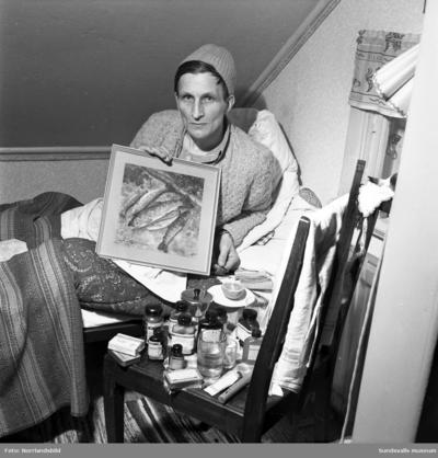Herbert Näslund, Skön, befinner sig i sjuksängen. En stol bredvid sängen är fullproppad med mediciner av olika slag. Han visar upp en tavla med fiskar på.