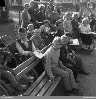 En grupp barn från Vanföreanstalten i Härnösand besöker Bergsåkers travbana, ett populärt utflyktsmål enligt reportaget i Dagbladet 1959. Tre av de som är med på bilden är: Gerd Söderberg, Sven Hellström och Emmy Tieusonen.