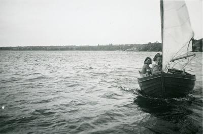 Två kvinnor seglar en mindre segelbåt. Landskap i bakgrunden.