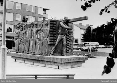 Sågverksmonumentet. Skulptur i koppar uppfört 1985 av konstnären Aston Forsberg (1922-2001) placerat på torget i Alnö centrum, till minne över sågverksepoken 1860-1963.