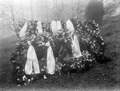 Nedanför en bergskant är ett flertal blomsterkransar med band, arrangerade.  I bakgrunden syns ett skogsområde i lätt dimma.
