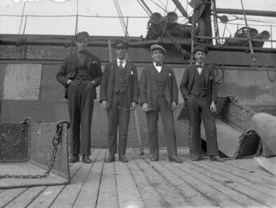 Fyra finklädda män står framför ett fartyg.