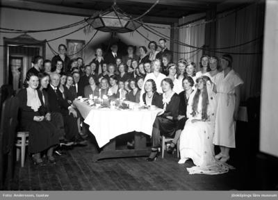 Ett Luciatåg och gäster har samlats runt ett dukat kaffebord för fotografering. I taket hänger en stor lampa, där girlander är fästa och som sträcker sig ut till väggen.