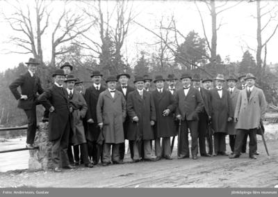 Nitton män i rock och hatt, några med paraply i handen, står på en väg vid ett räcke med skog i bakgrunden.