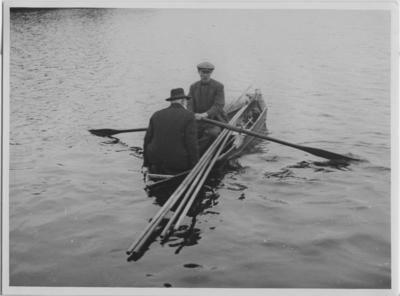 '2 män sittande i eka med tänger längs båtens sidor. Enligt bildtext: Pärlfiske i Lagan: Pärlfiskarna ro ut för att börja sökandet. ::  :: Ingår i serie med fotonr. 3744-3750.'