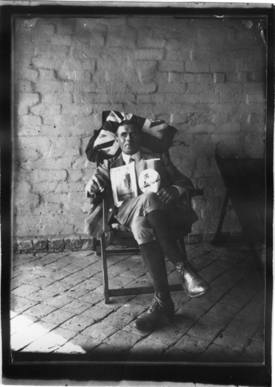 'Diverse fotografier från bl.a. dåvarande Nordrhodesia, nu Zambia, tagna av Konsul Magnus Leijer. ::  :: En man sittande i en stol vid väggen på en stenlagd veranda. Huvudet lutat mot en kude m brittiska flaggan. I händerna en tidning: ''The Rapid''.'