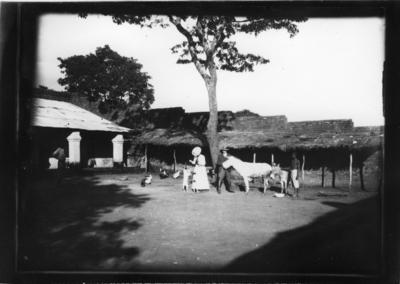 'Diverse fotografier från bl.a. dåvarande Nordrhodesia, nu Zambia, tagna av Konsul Magnus Leijer. ::  :: 1 st kvinna med hund och 1 st man med åsna, 1 st man bredvid med ytterligare en åsna. Dessutom fåglar och ytterligare 1 st man vid sidan, alla framför byggnad.'