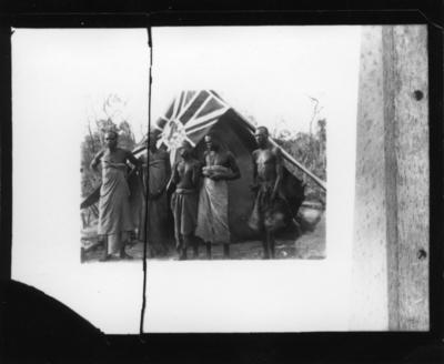 'Diverse fotografier från bl.a. dåvarande Nordrhodesia, nu Zambia, tagna av Konsul Magnus Leijer. ::  :: Fem män stående på rad framför ett tälr, på vilket en flagga ligger.'