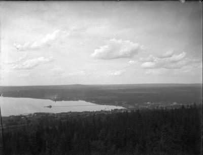 'Bildtext: ''Nedre från Vidablick 1917.'' :: Landskapsvy ut över hus och öppna fält, åkrar och vy med sjön Siljan med Långbryggan. I förgrunden granskog. ::  :: Ingår i serie med fotonr. 5232:1-8. Se även fotonr. 5223:1-13, 5231:1-12 och 5234:1-12.'