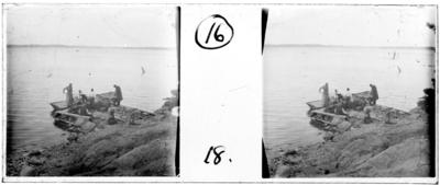 'Bildtext: ''Strömmingsvarp, Fru Möller och J.E. Frykberg.'' :: Vy med 7 personer samlade nere vid vattnet, kvinna, män, barn. Vid en eka, träbåt, i arbete med fiskenät. Kläder. Oskarp bild. ::  :: Ingår i serie med fotonr. 5254, se även hela serien med fotonr. 5237-5267.'