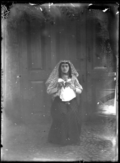 '1 kvinna håller upp sitt barn (bäbis, baby). Iklädd slöja, stående framför husvägg. Kläder. Klädsel. ::  :: Ingår i serie med fotonr. 5277:1-19. Se även fotonr. 5269-5292 med bilder från Stuxbergs resa till Kaukasien. Fotonr. 5277:3, 9, 11 och 15 är troligen samma motiv.'