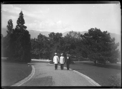 'Vy med 3 män stående på grusväg, grusgång i park. 2 av dem iklädda uniform. I bakgrunden träd och i fonden berg. Kläder. Klädsel. ::  :: Ingår i serie med fotonr. 5282:1-15. Se även fotonr. 5269-5292 med bilder från Stuxbergs resa till Kaukasien.'